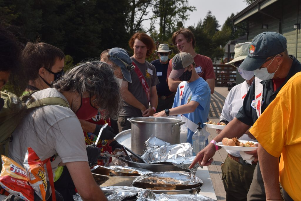 Picture of Scouts at a service table loading their dinner plates with food.