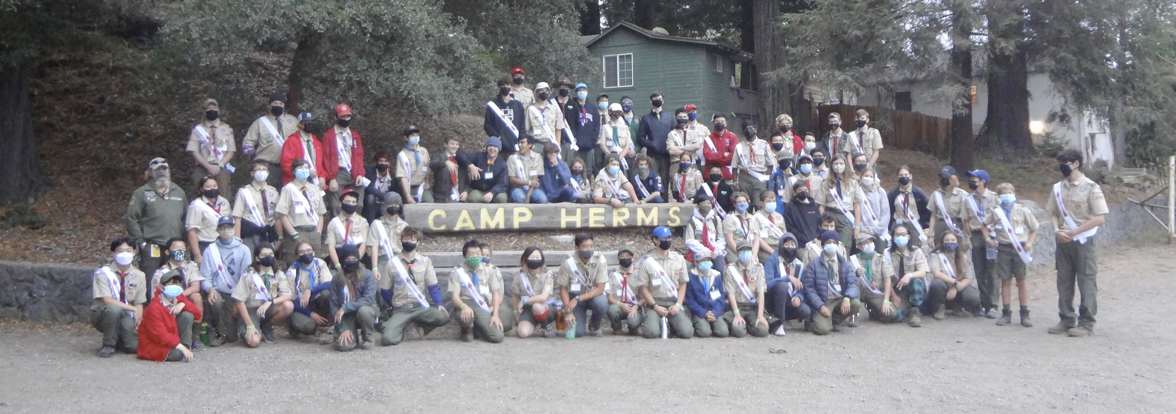 Arrrowmen pose for a photo in front of the Camp Herms sign at Induction Weekend