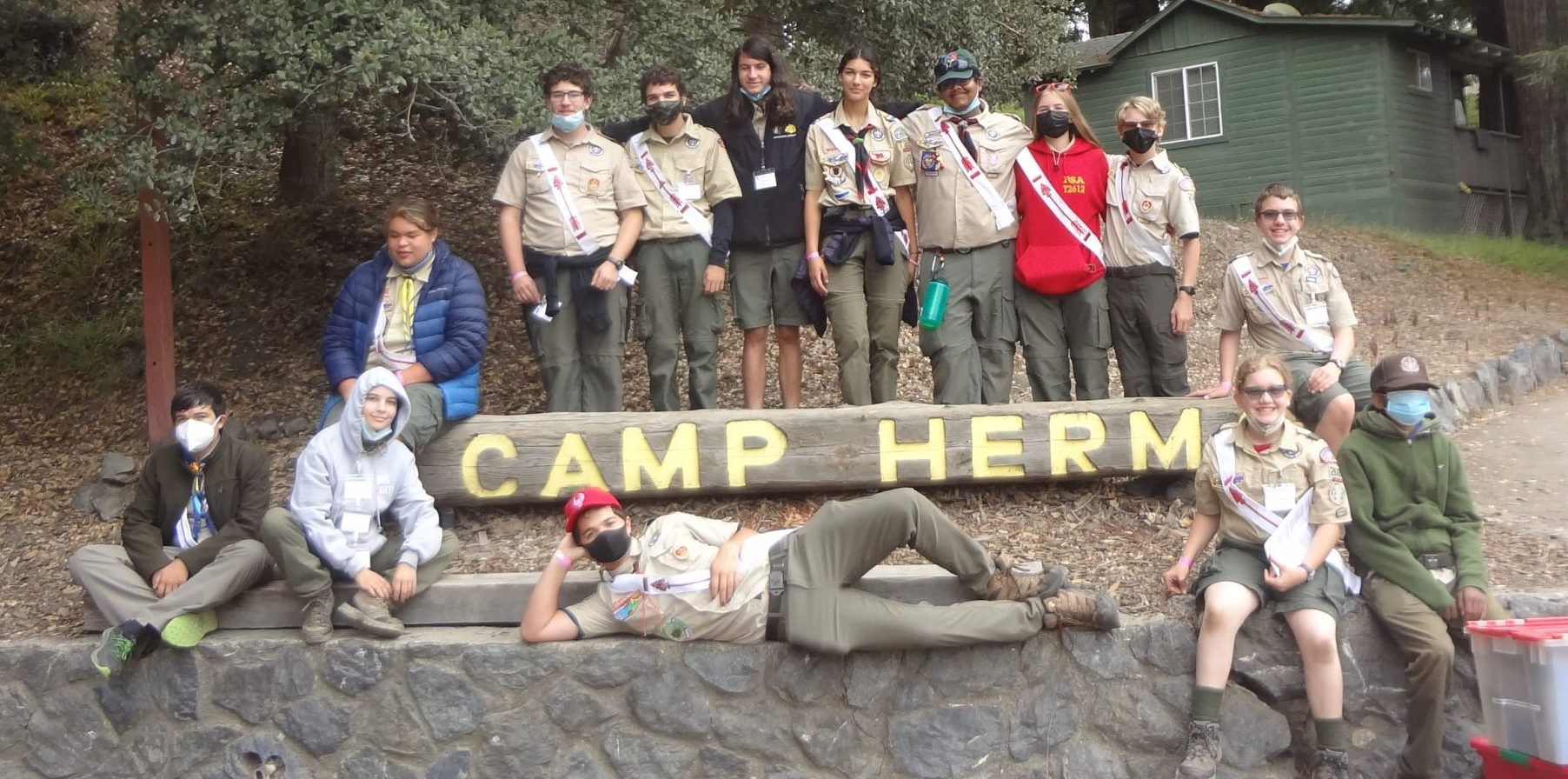 Staff of the 2021 Induction posing for a photo in front of the Camp Herms sign